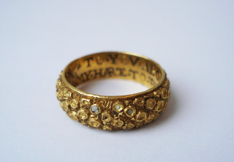 Posy-ring; gold; inscribed in black enamelled script; exterior covered with bosses, tops of which are filled with pale turquoise, white(?), enamel, of which some is lost.