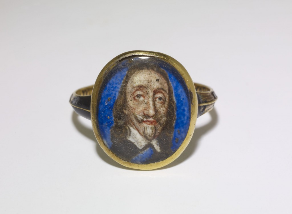 Finger-ring; enamelled gold, the oval bezel with portrait of Charles I on a blue ground, the sides with flutes in black enamel, the shoulders enamelled black. The back of the bezel is enamelled with a skull flanked by monogram, all in white on black, with a black enamel inscription inside the hoop.