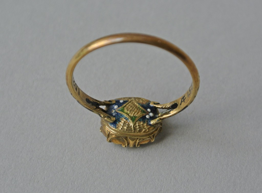 Mourning ring; gold; bezel containing rock crystal (or glass), beneath which is a monogram within looped border of gold thread over plaited hair; underside of bezel has lozenge enamelled in green upon ground of dark blue with white spots; enamelled on shoulders with blue lozenge with central white spot on ground of black enamel; each shoulder branches into three. No maker's mark.