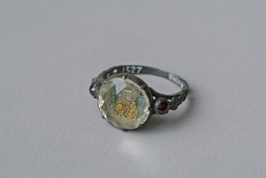 Mourning ring; silver; oval bezel reeded beneath and containing cipher in gold thread with basket in silver on a green fabric background, beneath rock crystal (or glass); each shoulder set with garnet and pierced with scrolls.Probably originally gilded. No maker's mark.