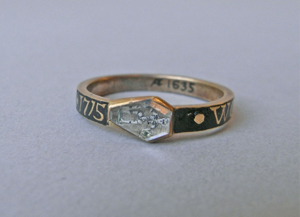 Mourning ring; gold; hoop with inscription reserved in black enamel; small coffin-shaped bezel with rock crystal over black and white enamelled skeleton holding arrow and hour-glass, upon background of hair. Green enamel on hour-glass and patch of ground on which skeleton stands. No maker's mark.