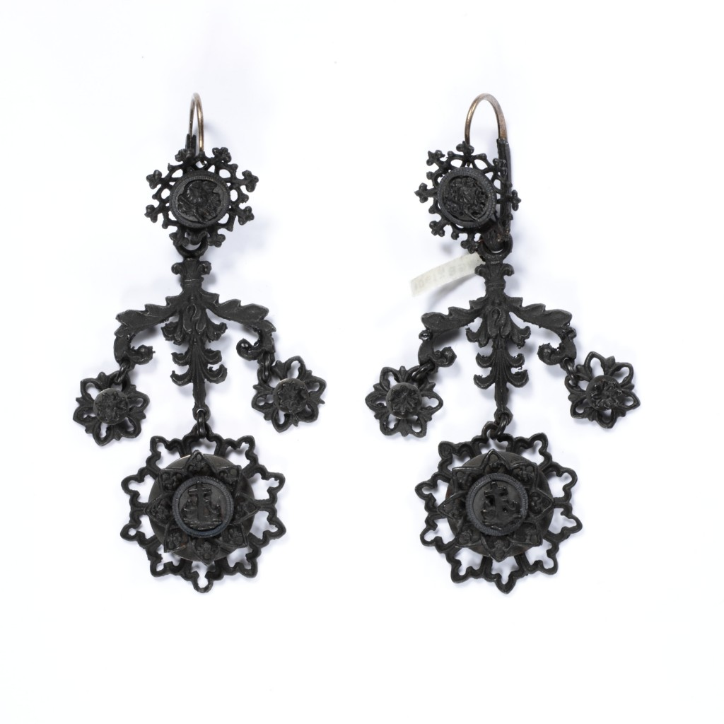 Cast-iron jewellery was an inexpensive but fashionable novelty for consumers in Europe and America from around 1800 to 1860. Developed in Germany in 1806–7 and often worn during mourning, it became the symbol of Prussian patriotism and resistance to Napoleon I in the Prussian War of Liberation fought from 1813-15. Women donated gold jewellery to their country in exchange for iron inscribed 'I gave gold for iron'.  The transformation of cast iron, a dark metal of little value, into a fashionable product was an important Prussian manufacturing success. Factories became adept at casting small, delicate parts which could be assembled to create the jewellery. A renewed interest in the medieval past throughout Europe brought stylistic change. After 1815, the Neo-classical designs of earlier Berlin ironwork were replaced by Gothic motifs such as the trefoil, quatrefoil, and fine pointed arches. The jewellery quickly gained an international profile. Demand peaked in the 1830s, when Berlin alone had 27 foundries and manufacture had spread to France and Austria.