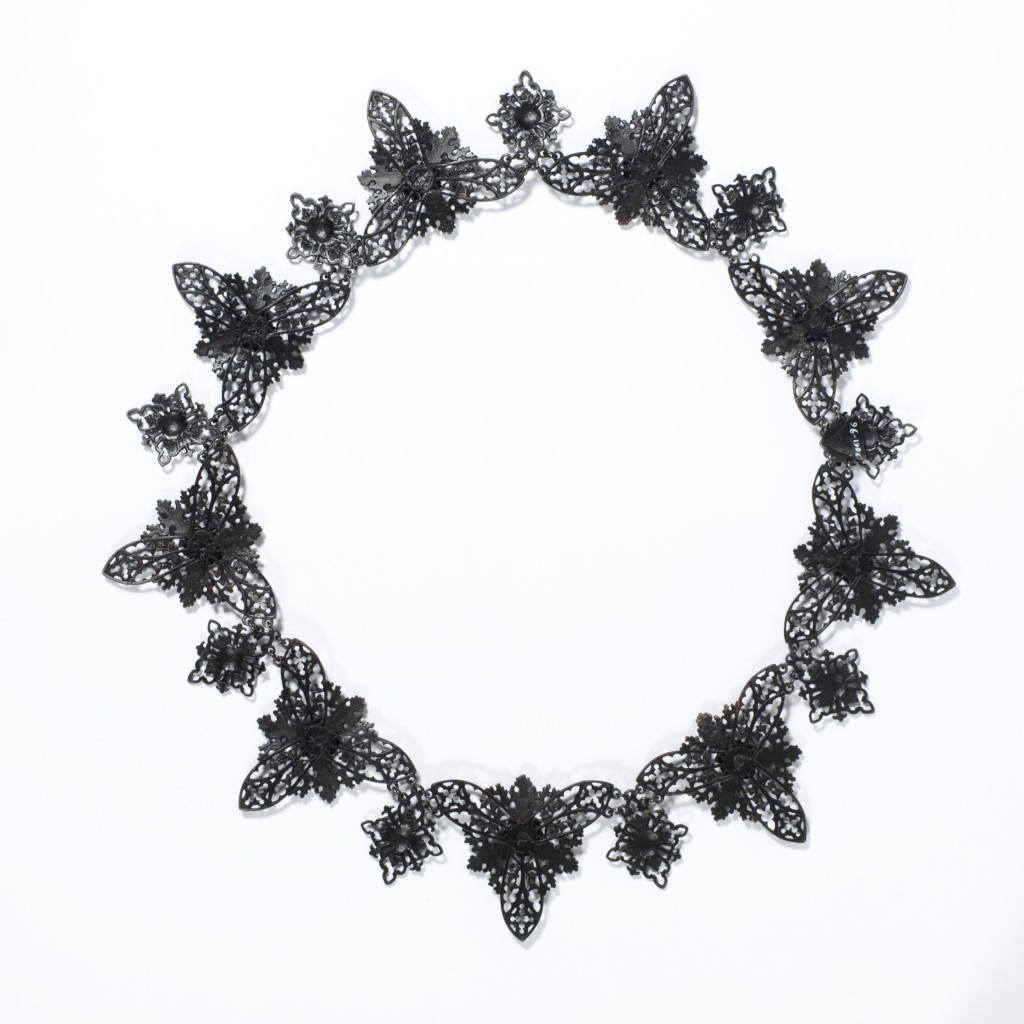 Cast-iron jewellery was an inexpensive but fashionable novelty for consumers in Europe and America from around 1800 to 1860. Developed in Germany in 1806–7 and often worn during mourning, it became the symbol of Prussian patriotism and resistance to Napoleon I in the Prussian War of Liberation fought from 1813-15. Women donated gold jewellery to their country in exchange for iron inscribed 'I gave gold for iron'.  The transformation of cast iron, a dark metal of little value, into a fashionable product was an important Prussian manufacturing success. Factories became adept at casting small, delicate parts which could be assembled to create the jewellery. A renewed interest in the Medieval past throughout Europe brought stylistic change. After 1815, the Neo-classical designs of earlier Berlin ironwork were replaced by Gothic motifs such as the trefoil, quatrefoil, and fine pointed arches. The jewellery quickly gained an international profile. Demand peaked in the 1830s, when Berlin alone had 27 foundries and manufacture spread to France and Austria.