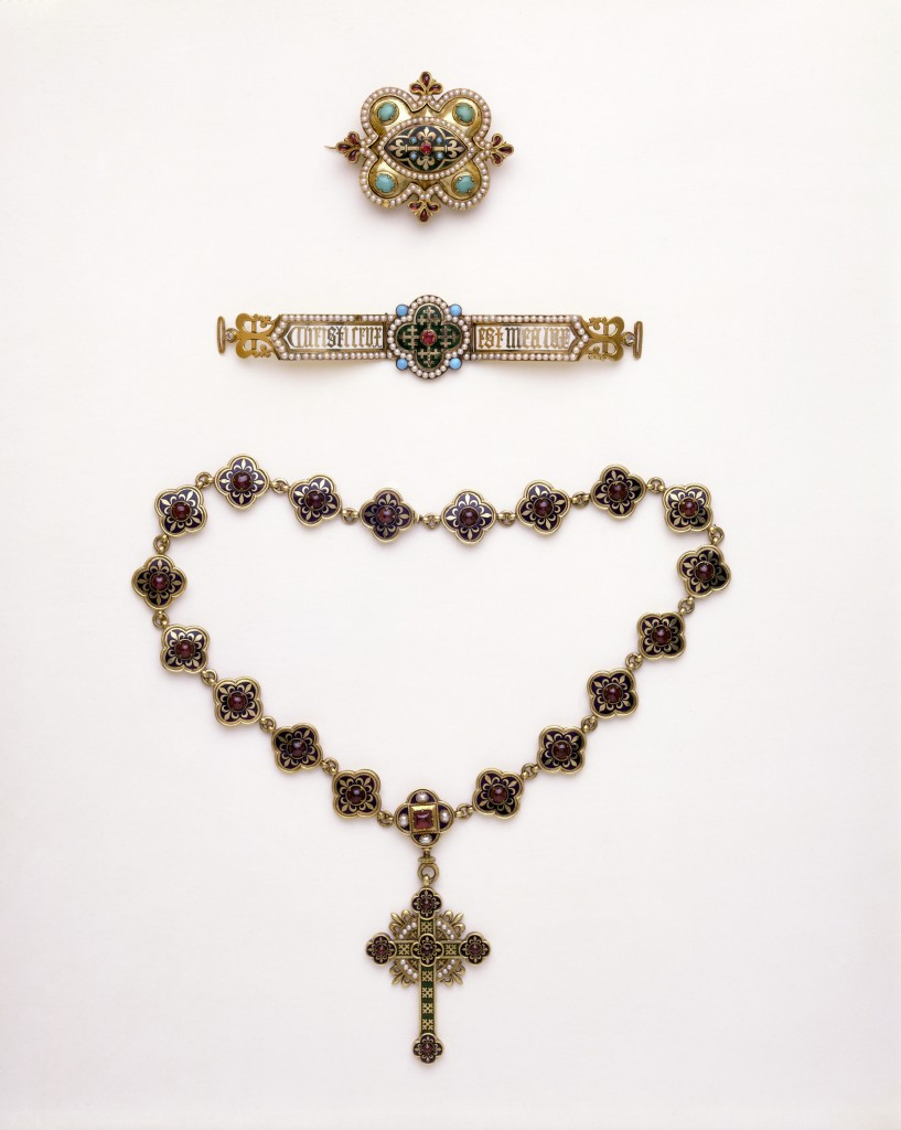 Object Type  The necklace is composed of 19 enamelled quatrefoils set with garnets. The pendant cross has quatrefoil ends decorated in the same manner as the links of the necklace. In each of the angles between the arms are four small pearls surmounted by a gold fleur-de-lis.  People  The necklace and pendant were made for Louisa Burton, the second wife of the architect A. W. N. Pugin (1812-1852). Pugin's account with John Hardman & Co. of Birmingham contains an entry on 21 December 1843 for 'A Gold enamel Chain & Cross' costing £47. 15s. Louisa died eight months later.  The cross and chain became part of the large parure (set) of jewellery prepared by Pugin for his intended third bride, Helen Lumsdaine. He persuaded Helen to convert to Catholicism, but in 1848, before they could be married, he was parted from her at the insistence of her relatives. Pugin subsequently married a Catholic, Jane Knill, on 10 August 1848. The society gossip Ralph Nevill recalled her as a very pretty woman, her every jewel mounted 'in a Gothic setting'. The set was exhibited in Pugin's Medieval Court at the Great Exhibition of 1851, where it was admired by Queen Victoria.