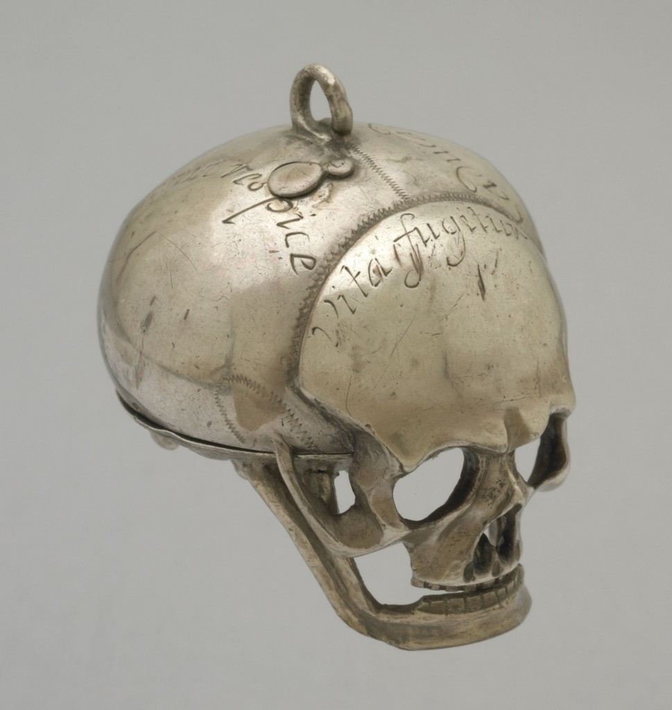 SILVER CASED VERGE WATCH IN THE FORM OF A HUMAN SKULL. . MOVEMENT FRAME: Full-plate with circular gilt-brass plates and four baluster pillars. : MAINSPRING & SET-UP: Gilt-brass barrel with tangent-screw set-up mounted on the potence-plate. : FUSEE & STOP-WORK: Gilt-brass fusee with chain and English stop-work. : TRAIN: Four wheel train, the contrate wheel solid. : ESCAPEMENT & BALANCE: Verge escapement, the crown wheel running between riveted potence and counter-potence. There have been extensive alterations to both potence and counter-potence suggesting that the crown wheel is most likely to be a replacement. Verge and steel 2-arm balance not original. The pierced and engraved gilt-brass foliate balance cock is also a replacement. There are a number of vacant holes,both threaded and plain, in the potence-plate where it appears that the original balance cock was replaced by a balance bridge and balance spring. : DIAL & HAND: An engraved border on the front of the pillar-plate surrounds the pinned-on silver dial which has Roman hours I-XII, arrow-head half-hour marks and a quarter circle. The blued-steel hand is a replacement. : CASE: Silver case in the form of a human skull, the lower plate, including the lower jaw being hinged at the back. On top there is a cover for the winding hole. Silver hanging loop. There are inscriptions in various places on the outside of the skull. Movement hinged to case at XII.