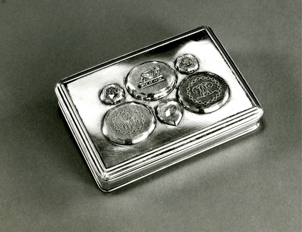 Silver box with mouldings on edge of lid and base with a gilt interior and a hinged lid: set with five memorial ovals and one in the form of a heart, on corded silk under faceted rock-crystal. One shows an enamelled skeleton with an inscription and the others consist of gold wire monograms.