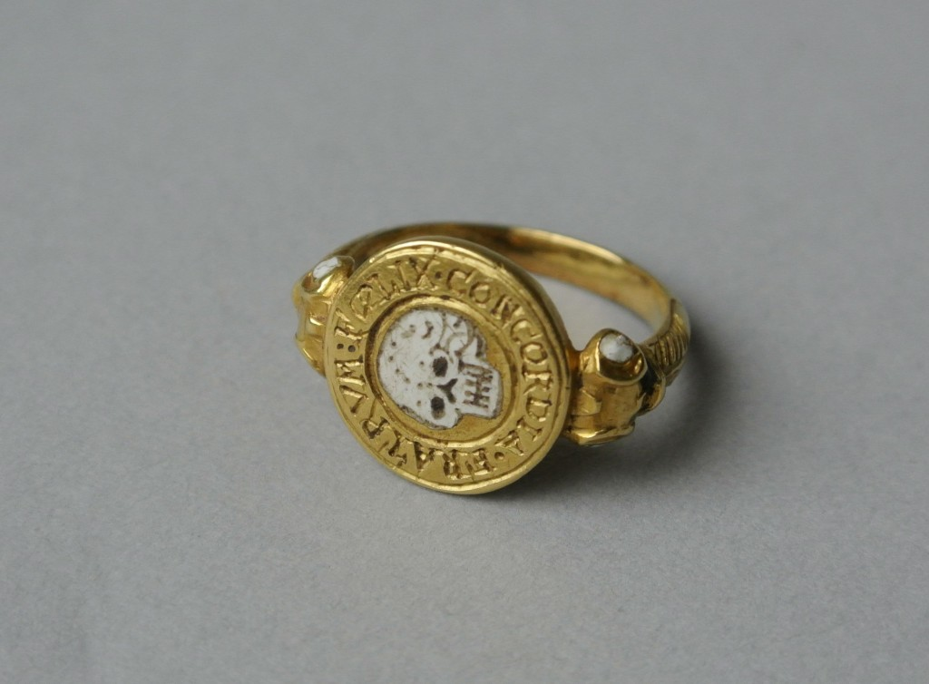 Mourning-ring; gold, with circular bezel containing enamelled skull (death's head) surrounded by the Latin legend: FOELIX CONCORDIA FRATRUM. The shoulders of the hoop are scrolled and ornamented with white and green enamel. At the back of the bezel are three engraved letters, H, above I and A. No maker's mark.