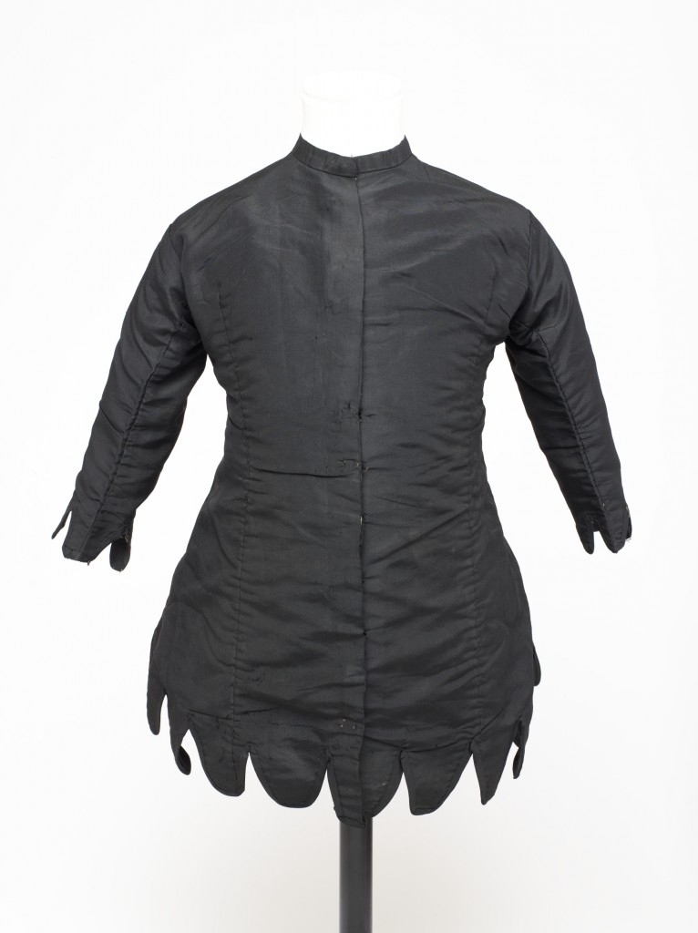 Little girl's mourning garment, in the form of a short princess-line coat dress made of black grosgrain lined throughout with white cotton. The garment has a rounded neck with a self fabric neckband, and fastens the length of the front with metal hooks and stitched loops. The hem and wrist-length sleeves are finished with vandyke tabs bound and faced with self fabric. The coat is shaped to fit at the waist: it is cut in six pieces, the front two of which have long darts. Lines of stitch holes indicate that two mitred pieces of fabric which were originally positioned at the waist back have been removed.