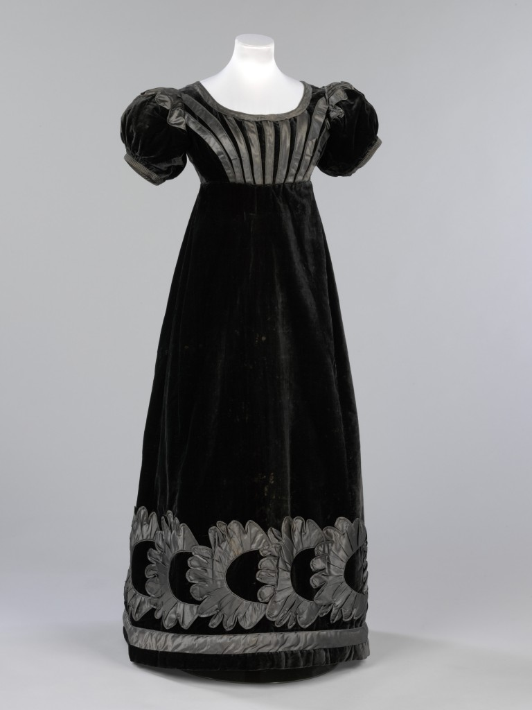 This black velvet evening dress was worn Jane Johnstone (1803-1847), niece of William Jardine founder of Hong Kong merchants Jardine, Matheson & Co. The wide neckline and short sleeves of the dress are typical of fashionable evening wear of the mid 1820s. Although it retains remnants of the high-waisted, neo-classical shape popular at the beginning of the century, its construction shows the move towards the lower waists and fuller skirts of the 1850s. The use of velvet demonstrates the trend for more sumptuous fabrics after the dominance of cotton and muslin in the previous two decades. The death of Princess Charlotte, the only child of George IV, in childbirth in 1817 plunged the whole country into mourning and set the high standards for mourning dress of this period. Fabrics such as silk and velvet were too shiny to be worn for the first stages of mourning, however, official mourning guidelines issued by the Lord Chamberlain decreed that black velvets and silks were permissible in the third and final stage. This dress would have been worn with an evening turban, long gloves and a pelisse cloak, often lined with chinchilla fur. It is likely that it was a gift from William Jardine and was worn when mourning the death of Jane Johnstone's grandmother, Elizabeth Johnstone who died in 1825.