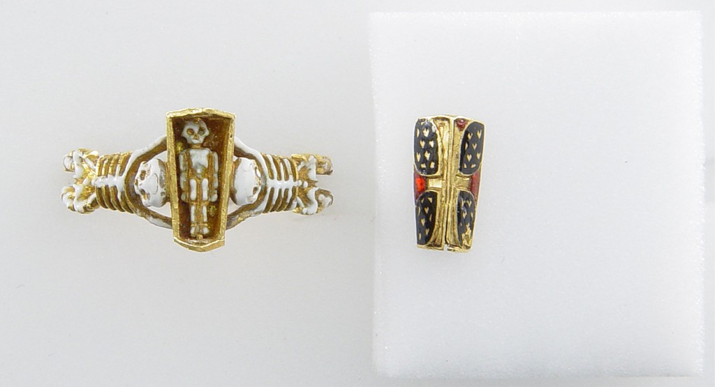 Mourning-ring; enamelled gold, the hoop enamelled white, in the form of two skeletons supporting a coffin-shaped bezel with moveable lid (now separate) fastened with a pin (now missing) and ornamented with a Maltese cross once enamelled red, on a black ground with hearts reserved in the metal, an enamelled cinquefoil at one end. Inside the coffin is a tiny white-enamelled skeleton. At the back of the bezel ares two clasped hands. No maker's mark