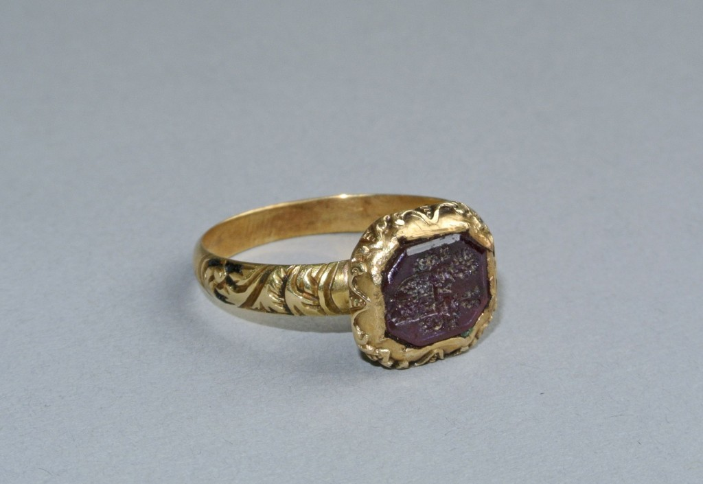 Mourning ring; gold; panel with scrolls on each shoulder, on ground of black enamel; bezel hexagonal containing garnet engraved in intaglio with German shield of arms; quarterly 1 and 4, 2 and 3 a lion rampant; above, two crested helms and monogram; ornamented on sides by flutings filled with black enamel with white dots. No maker's mark.