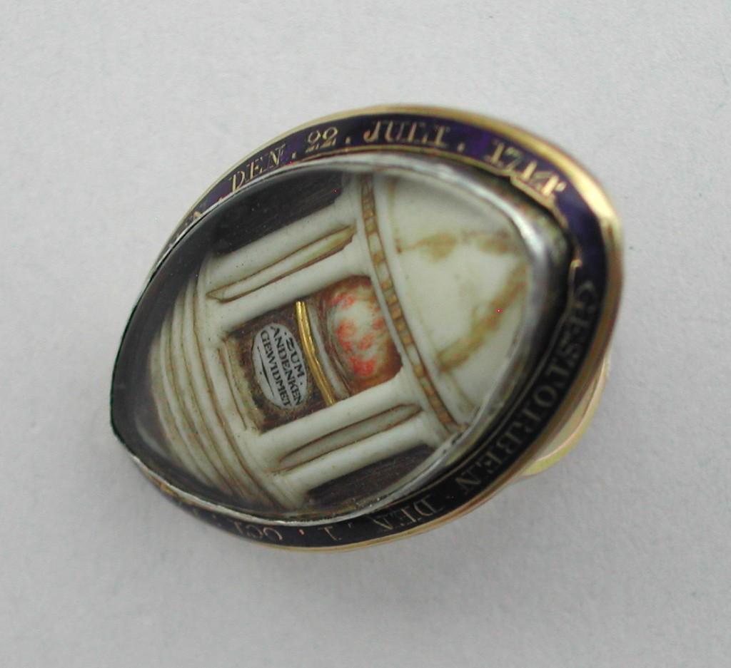 "Large navette shaped 15K gold ring, with 3-D ivory and gold mausoleum with a rounded dome and classical columns, enclosing an eternal flame, and bearing the inscription, ""zum andenken gewidmet"", (""dedicated to the memory of"") upon an altar decorated with gold wires and hair. Strands of hair are also laid along the sides of the mausoleum, as well as on some of the steps. Around the bezel is cobalt blue enamel with gold letters giving the birth and death dates of the individual in German: Gebohren den 22 Juli 1714 Gestorben den 1 Oct. 1783 (Born the 22 of July 1714, died the 1 of Oct. 1783). Part of the setting has been pried up, and the bezel and glass covering (replaced from old celluloid cover), can be easily lifted out. The shank is plain, and tapers to a narrow band. I'm guessing it's English made for a German client."