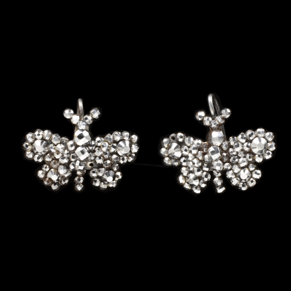 These butterfly earrings are typical of the cut steel goods exported from France to much of Europe and America in the second half of the nineteenth century. The flourishing trade was bolstered by the need for jewellery to wear during periods of secondary mourning (an interim period between full and semi-mourning in the Victorian era) as well as by fashionable status. In London in 1882 it was reported that steel butterflies had begun to perch on bonnets.