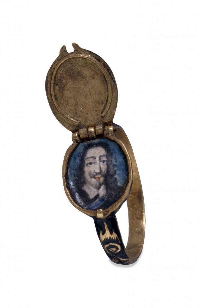 This gold ring has an oval bezel that opens to form a concealed locket, containing an enamelled portrait of Charles I (reigned 1625-49). The hinged lid is set with a diamond on an enamelled ground.  Commemorative jewellery depicting royalty was usually produced after the monarch's death, but was occasionally available during their lifetime, to be worn as a demonstration of loyalty. Commemorative jewellery, in the form of rings, lockets or hair clasps, was produced in great numbers after Charles' execution on 30 January 1649. Many examples have hinged lids: supporters of the Royalist cause, who wished to keep their allegiance secret, probably wore these during the Commonwealth under the rule of Oliver Cromwell. The Restoration of the monarchy in 1660 again produced great numbers of commemorative jewellery, made for those who claimed to have been Royalist supporters all along. Some rings commemorating Charles I were presented during his lifetime by his Queen, Henrietta Maria (1609-69), to Royalist supporters in appreciation of their continuing loyalty and financial backing, to be redeemed when the Civil War had ended.  Much commemorative jewellery is decorated with black enamel in the same fashion as mourning jewellery. The shoulders of this ring have a scroll pattern reserved in gold on a ground of black enamel, the diamond is bordered with black enamel, and the border of the bezel is decorated with a black and white enamelled pattern.  C. Oman, British rings 800-1914 (London, Batsford, 1974)