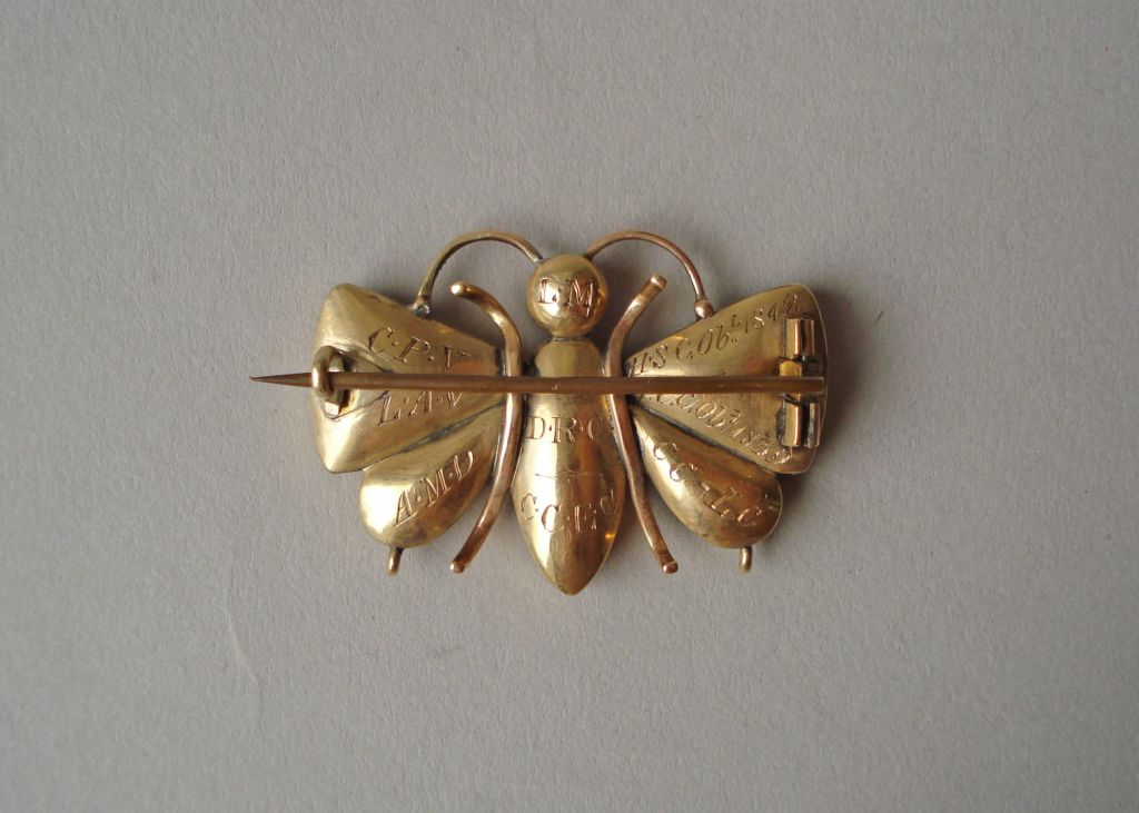Gold brooch in the form of a butterfly, with seven plaited hair arrangements under glass, two for each wing and three for the body. The gold mounts with engraved decoration. The reverse inscribed with initials and the date 1839 and 1842.