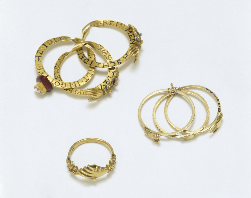 A gimmel ring made of three interlocking hoops. When worn the diamond-set heart at the front of the ring is encircled by a pair of clasped hands