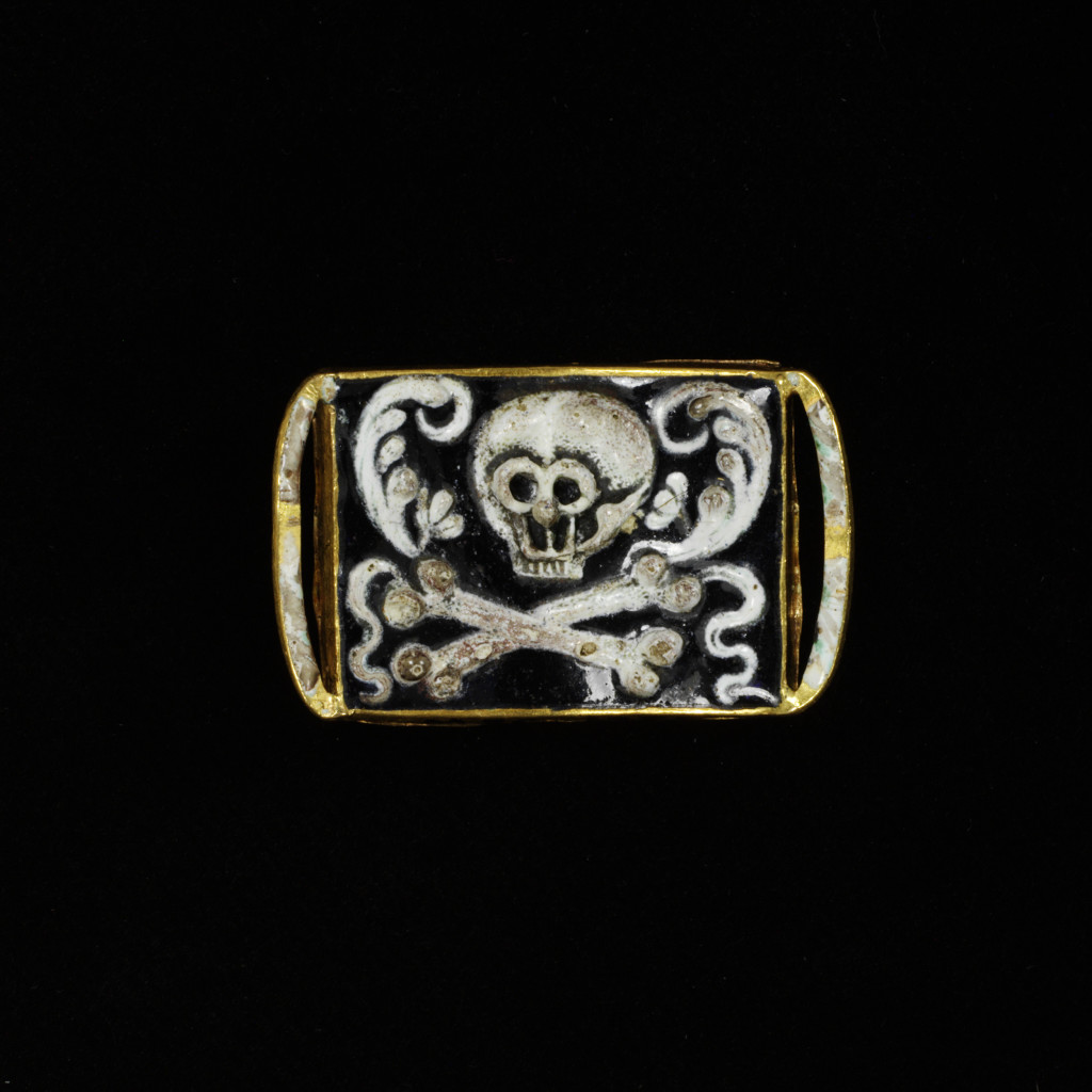 Pierced gold mourning slide, with enamelled skulls, crossbones, a winged heart, flowers and leaves.