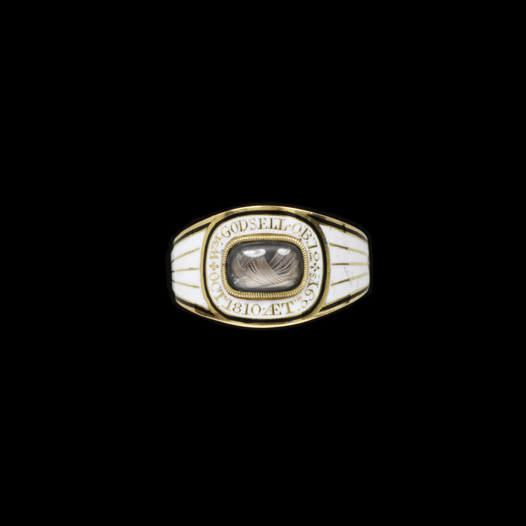 Gold mourning ring enamelled in black and white. The shaped rectangular bezel set with plaited hair. The border inscribed W M GODSELL. OB: 12.OCT: 1810 AET: 39 YS.