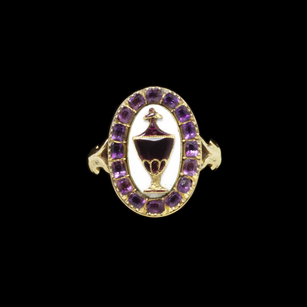 Gold mourning ring, enamelled in white and set with amethyst pastes. The shaped oval bezel with an urn decorated with transluscent enamel on white. Inscribed behind GEO/ NASSAU/ ARM/ OB:18. AUG 1823/ AET: 66..