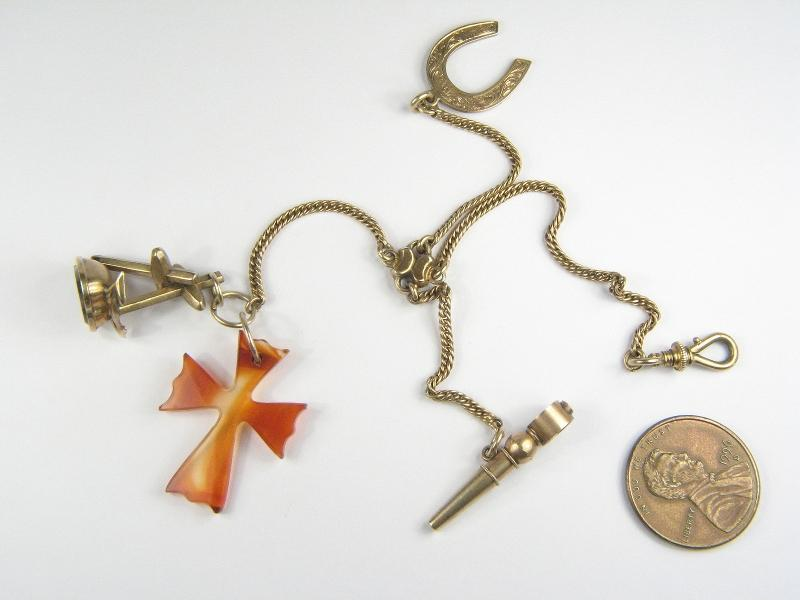 A good quality antique English, solid 9 carat gold (tests thereabouts) miniature chatelaine or fob; with four gold chain strands, each holding a 9 carat gold charm - a dog clip fastener, a horseshoe charm, an anchor, cross & heart shaped fob (Faith, Hope & Charity), a hand carved translucent agate cross charm and a Breguet type watch key fob.