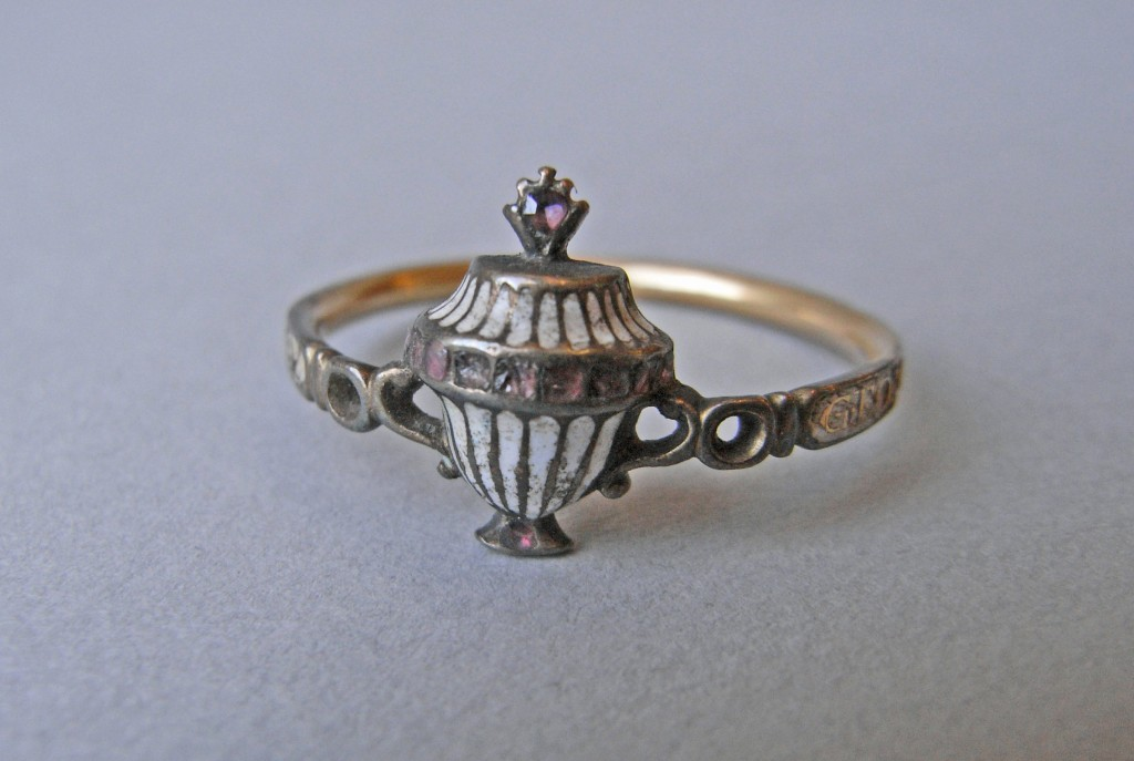 Mourning ring; gold; inscription on white enamel; bezel in form of urn enamelled white and set with pale garnets; hoop pierced with loops at shoulders. No maker's mark.