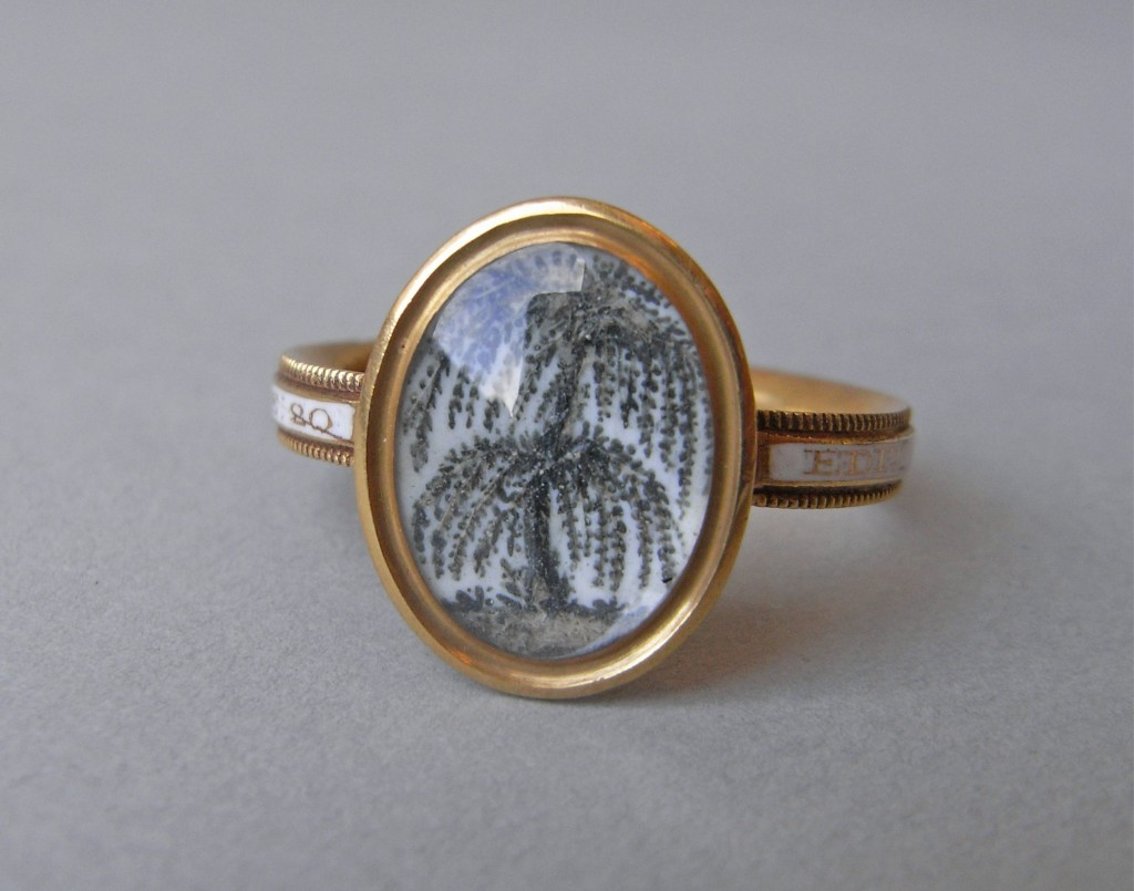 Mourning ring; gold; oval bezel with tree in hair on white ground; inscription on white enamel. No maker's mark.