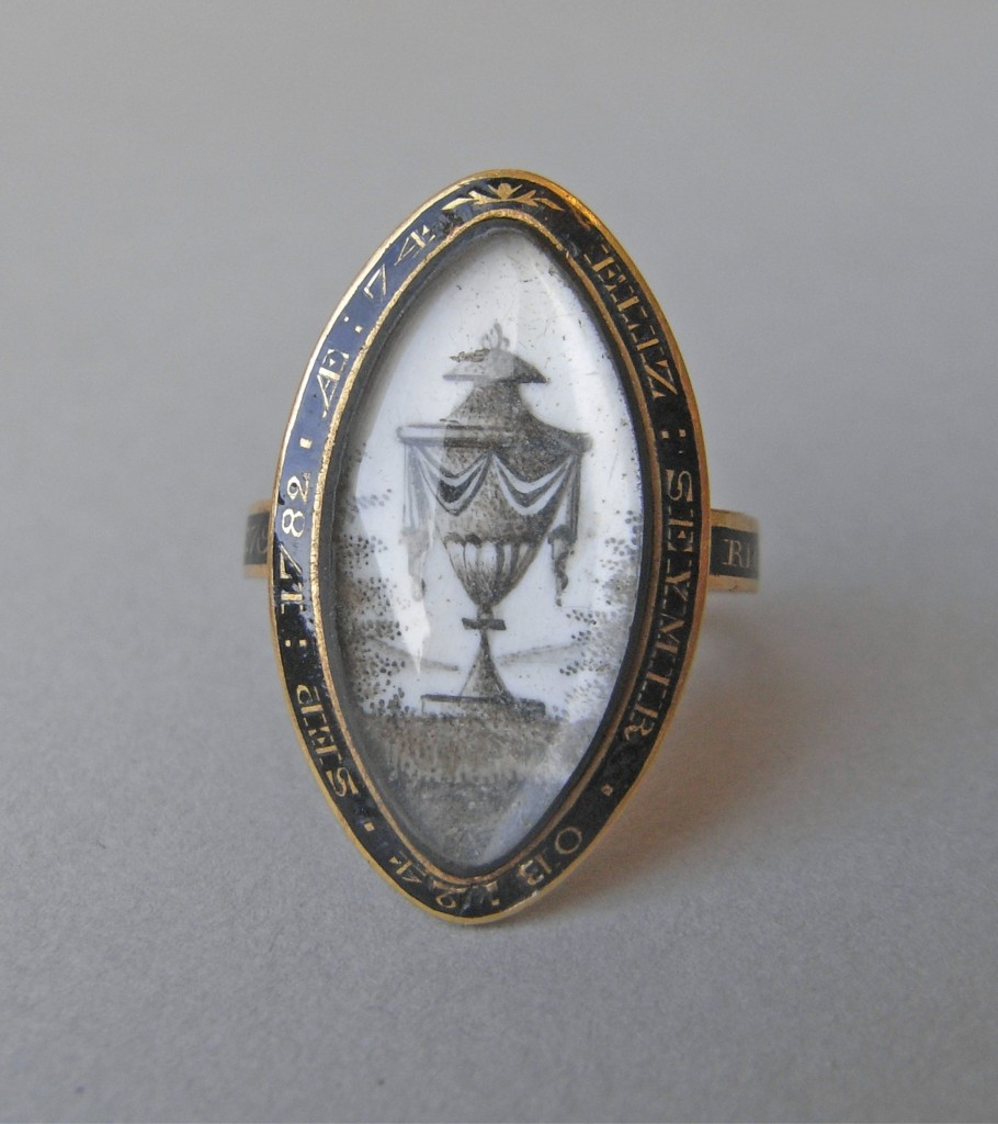 Mourning ring; gold, with pointed oval bezel containing urn and landscape partly painted and partly executed in cut and laid hair on a white ground, all under glass. The border and hoop have bands of black enamel with reserved inscriptions. No maker's mark.