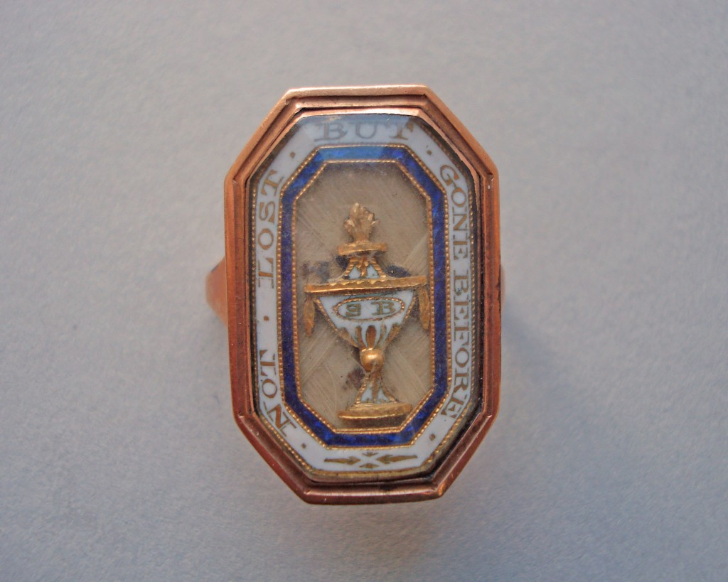Mourning ring; gold; octagonal bezel containing, under glass, urn in gold and white enamel inscribed with monogram, on plaited hair; border of blue and white enamel with inscription on the white. Inscription on back of bezel. No maker's mark.