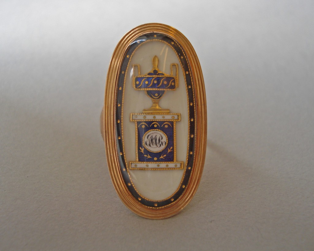 Mourning ring; gold, with large oval bezel containing on white ground an urn on pedestal in gold enamelled in blue and white, the pedestal bearing a monogram MR, black enamelled border with gold pellets, all beneath glass. Memorial inscription on back of bezel. No maker's mark.