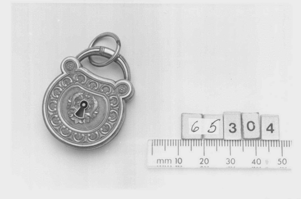 Provenance: Locket given by Mary, Duchess of York to Queen Victoria, 1900. Description: Chased gold locket in the shape of a padlock.