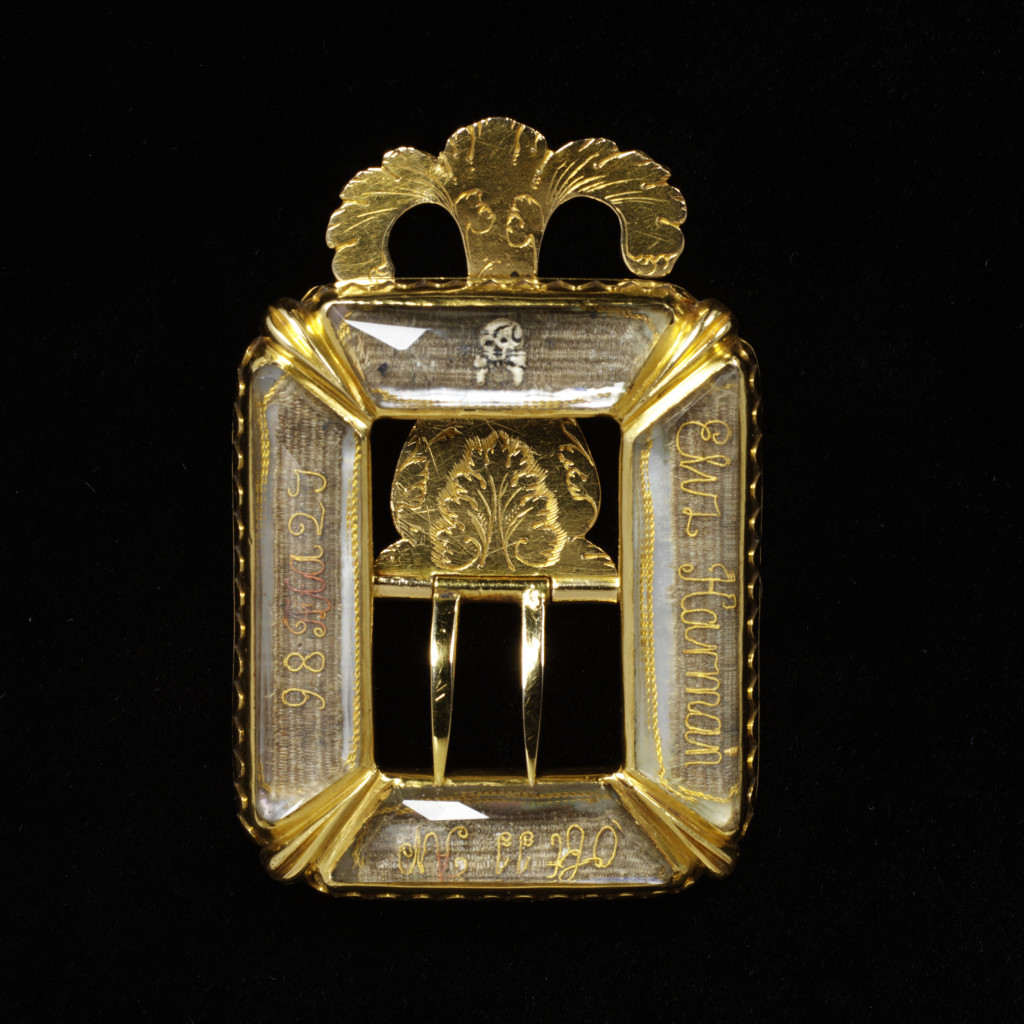 This mourning buckle contains panels of woven hair, decorated with an elaborate inscription in gold thread and a small enamelled skull, all set behind rock crystal. The inscription, partly in latin, tells us that the piece commemorates Elizabeth Harman who died on 11 April 1698, aged 27.