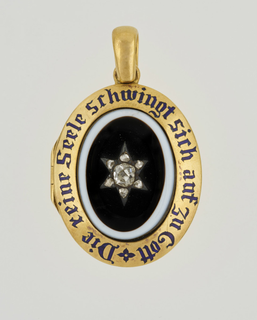 A small gold memorial locket, set with central oval onyx, black on white, with diamond star set in plain gold border with blue enamel inscription, 'Die reine Seele schwingt sich auf zu Gott', roughly translated as 'The pure soul flies up above to the Lord'. Opens to reveal hair on one side and photograph of Prince Albert on the other, both under glass.