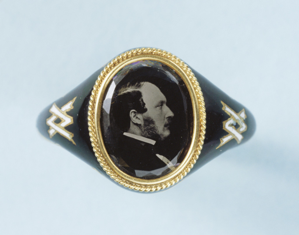 Memorial ring in gold and black enamel, the bezel containing a microphotograph, reversed, of the Prince Consort in 1861, which is attributed to J.J.E. Mayall. The cypher linking the initials 'V' and 'A' in white enamel is set into the shanks on either side of the bezel