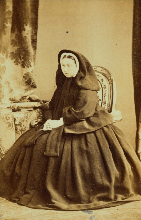 Full-length seated portrait photograph of Queen Victoria in mourning for Prince Albert. The Queen is holding a picture of the Prince in her right hand, is dressed in a black cloak and shawl over her head. There is a table with books to the side and curtains behind the Queen.
