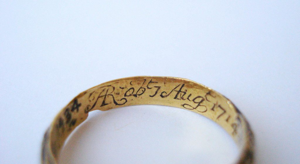 Mourning-ring; gold; oval bezel containing monogram in gold thread with letters under crystal; round hoop, reserved in metal on ground of black enamel, hour-glass, spade and pick crossed, cross-bones and skeleton; engraved inscription. No maker's mark.