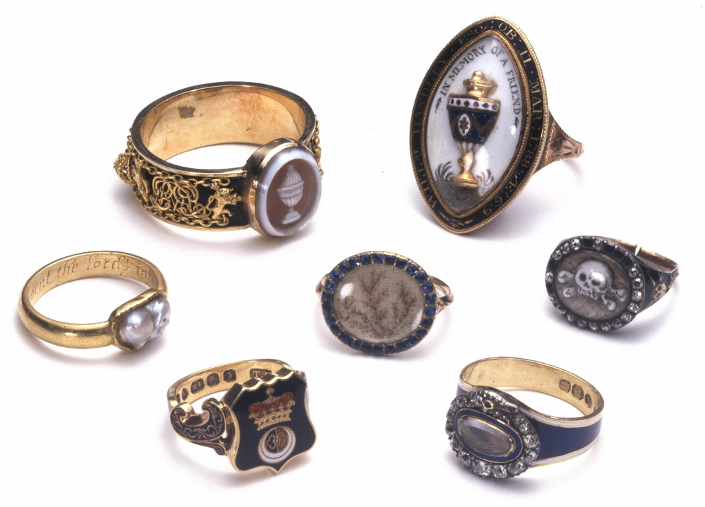 Mourning-ring; gold; bezel an oval setting containing onyx cameo with urn; round hoop on ground of black enamel, between chain borders, a royal crown twice repeated, with supporters lions crowned rampant, and monogram repeated three times; design terminated towards bezel on each side by crowned lion rampant; engraved inscription. No maker's mark.