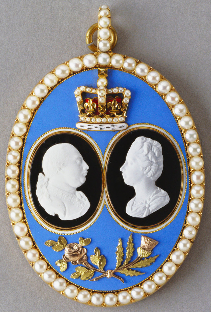 Large oval pendant with two small white cameo profiles of George III and Queen Charlotte applied to black enamel ovals, mounted on pale blue enamel plaque with applied crown above and entwined rose and thistle below; all within a border of seed pearls. Cypher in gold on reverse.   This pendant is said to have been presented by the King George III and Queen Charlotte to the Hon. Georgiana Townsend (1761-1835), eldest daughter of Thomas, 1st Viscount Sydney, who had, as leader of the House of Commons, taken a prominent role in arranging terms of peace with America in 1783. It was his cousin Charles Townsend who had ignited unrest in the American Colonies by introducing the hated Stamp Act in 1765. Lord Sydney was twice Secretary of State; and in 1790 the newly discovered harbour of Sydney, Australia, was named after him.  Georgiana had known the royal family since she was a young girl and was friendly with the Queen and the Princesses. In 1801 she was appointed to the sinecure of State Housekeeper at Windsor, a position she retained for the remainder of her life. Her residence was the Norman Tower, Windsor Castle. The pendant was among a number of objects acquired by Queen Mary from the sale of the Sydney collection in 1915.