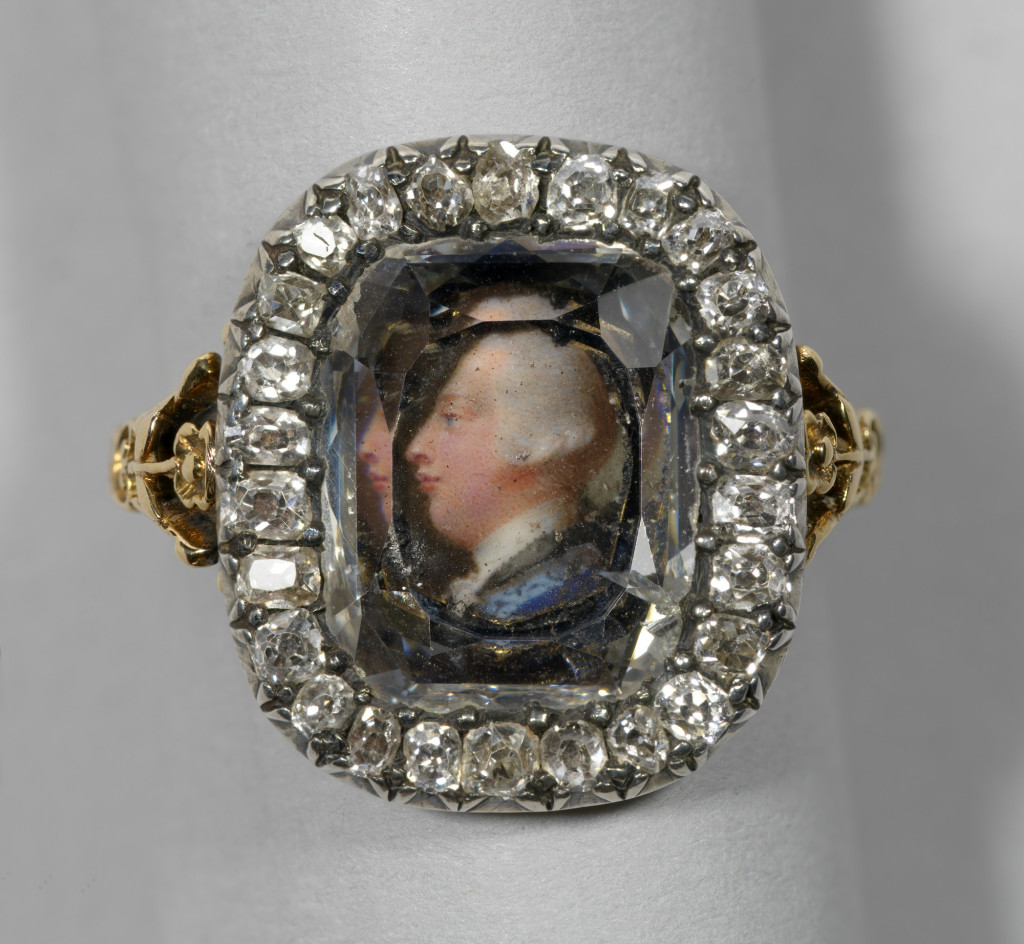 This ring formed part of a suite of jewels given to Queen Charlotte by the King on their wedding day, 8 September 1761. Charlotte Papendiek records that this ring is set with the 'likeness of the King in miniature, done exquisitely beautiful for the coin, by our valued friend Jeremiah Meyer' and was 'given also to her Majesty to wear on the little finger of the right hand on this auspicious day'. The Queen also received 'a diamond hoop ring ... a pair of bracelets, consisting of six rows of picked pearls as large as a full pea; the clasps - one his picture, the other his hair and cipher, both set round with diamonds; necklace with diamond cross; earrings, and the additional ornaments of fashion of the day'.