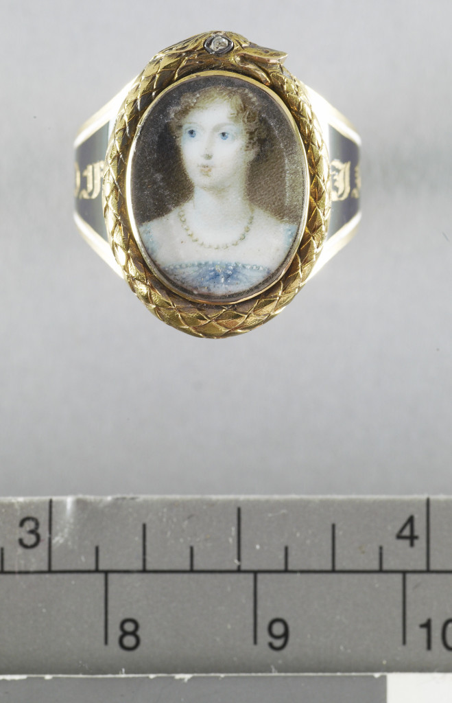 Mourning ring mounted with glazed oval miniature of Princess Charlotte (1796-1817) within a frame of a gold ouroboros with a diamond eye, the band enamelled in black and white with a mourning inscription 'IN MEMORY OF PRINCESS CHARLOTTE 1817'.  This miniature, which in terms of technique is consistent with Jones's work, is based on a miniature by her dating from 1813. The primary evrsion, in the Palais Royal. Brussels, shows the Princess, standing, with Westminster Abbey in the background on the left and was used as a basis of a stipple engraving by John Agar. Another version is at Anglesey Abbey. This miniature shows the Princess wearing a pearl necklace rather than the more elaborate emerald and pearl necklace in the source.