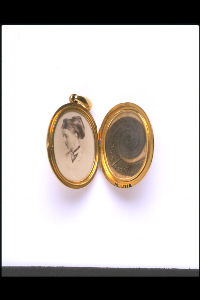 A jeweller made this locket to commemorate someone who had died. The back of it is inscribed 'In remembrance of L.B.F. Oct 7th 1871, from C.G.S.F.'. The widowed husband of the woman in the photograph probably bought the locket and gave it as a keepsake to one of his wife's close friends or relations. Lockets were particularly fashionable items of jewellery from about 1860 to1880 and they have remained popular ever since.