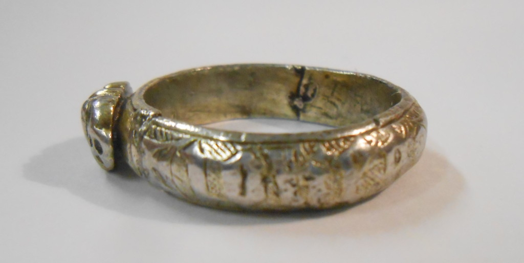 Silver gilt ring, the applied bezel with a heart between two death's heads. The hoop engraved with a worm and inscribed in black letter + iohes godefroy