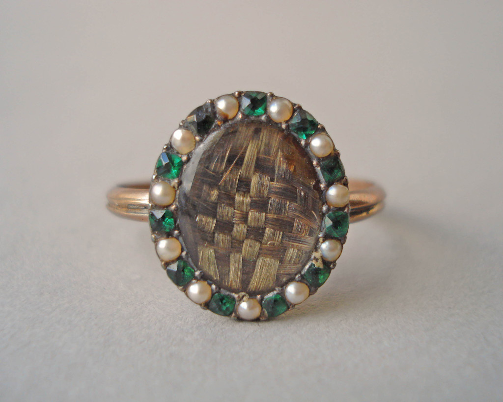 Mourning ring; gold; slender channelled hoop; oval bezel containing plaited hair covered with convex glass; border of seed pearls alternating with emerald pastes. No maker's mark.