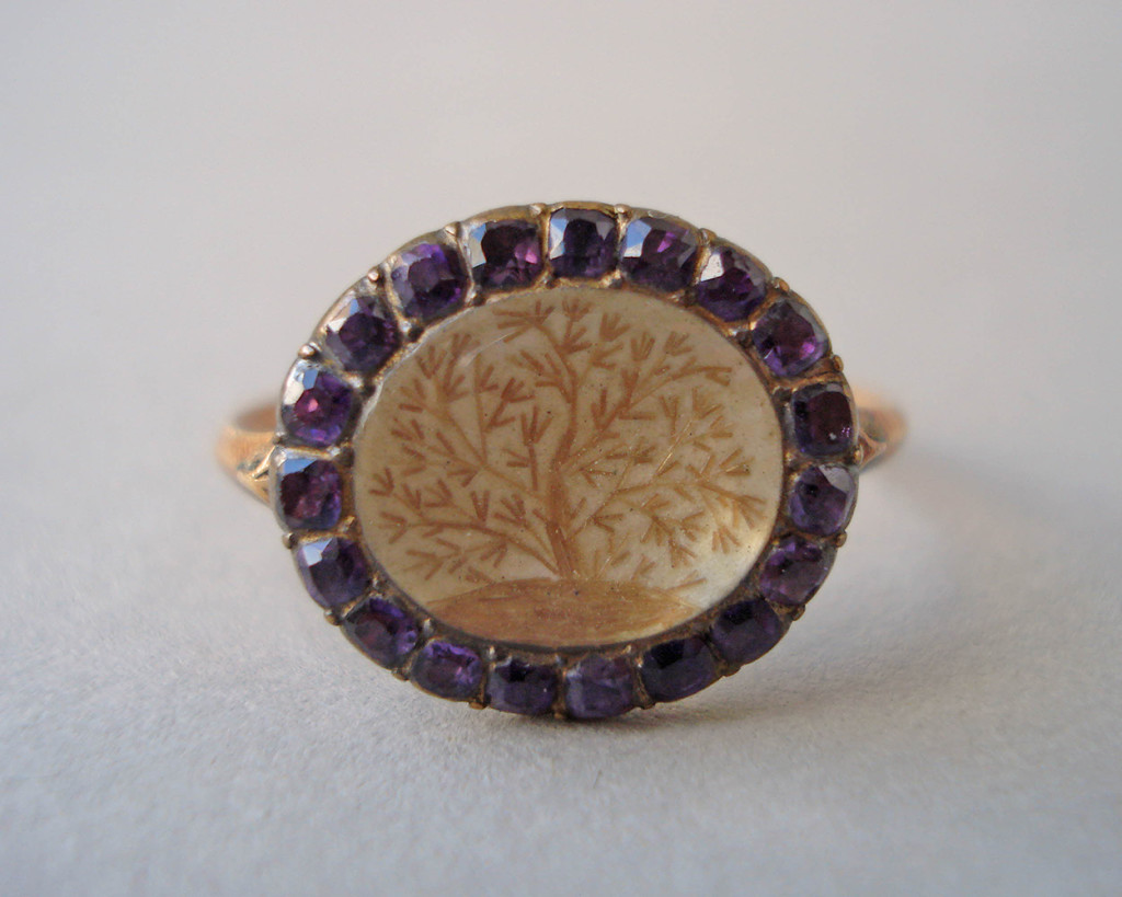 Mourning ring; gold; plain slender hoop; oval bezel, reeded beneath, containing tree embroidered in hair upon a white ground all beneath crystal and surrounded by border of amethysts. No maker's mark.