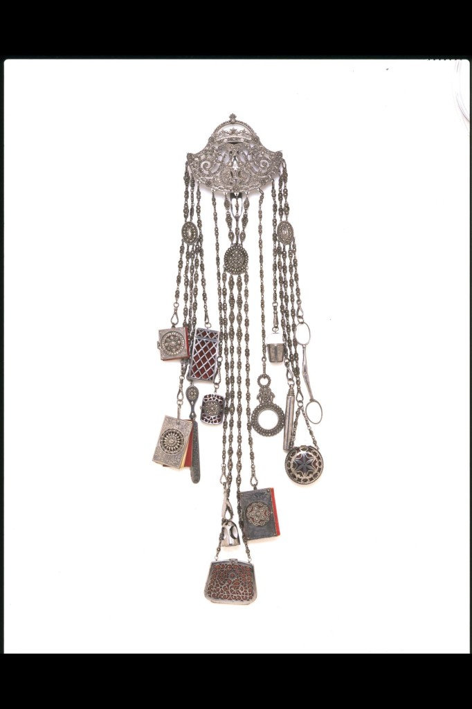 A chatelaine would have hung from a lady's waist and was intended to be both decorative and practical. The small tools and accessories that might be incorporated included a watch, scissors, tweezers, magnifying glass, scent flask and miniature notebook or ivory writing tablet. Cut steel was a fashionable material for jewellery, buttons, buckles, sword hilts and watch chains in the decades around 1800. They were made from brightly polished rivets, their ends faceted to imitate diamonds. Such pieces gave a grey but powerful glitter. Originally an English speciality, the production of cut steel had spread to other centres in Europe by the early 19th century. The crowned monogram decorating the hook-plate has not been identified.