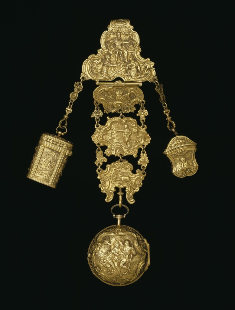 The top part of the chatelaine has a long hook at the back by which it would have hung from the belt of a fashionable lady. The chatelaine has London hallmarks on the hook, so it can be dated precisely to 1755-6. There are three objects suspended from the chatelaine. In the middle is a watch, which bears the name of the watchmaker, Robert Cawley, Chester, movement no. 91. The watch and the small empty container or étui on the right are of approximately the same date as the chatelaine. To the left is a container or étui for snuff, which dates from about 1730. It contains a small gold spoon for ladling out the snuff and a 19th century watch key. The chatelaine and the watchcase are decorated with figure scenes. On the chatelaine there are scenes from the life of King David as described in the Bible. On the watchcase is a scene of Angelica and Medoro carving their initials in a tree, taken from the epic Orlando Furioso by the Italian poet Ludovico Ariosto (1474-1533).