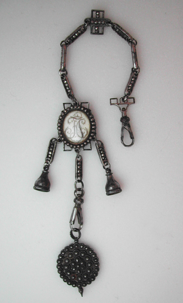 "A French chatelaine of cut steel, c. 1770-1780, with oval glazed compartment, one side showing initials in hair (FJC) on an ivory background, the other with a wheat sheaf, also from hair on ivory, showing three broken stalks and three birds in flight above. The top has a swivel spring clip, the bottom has an oval cut steel medallion attached to a second swivel spring clip. The links are attached with faceted split rings. There are two side bell caps; whatever was there originally is now missing- perhaps seals? There are holes around the tops of the decorative twist on the caps- perhaps something was pinned inside? Very good condition, hairwork is pristine, end of steel medallion missing half of small finial, one steel facet missing at 6 o'clock on the wheat sheaf side surround. Some rust, mostly to bottom medallion. Measures 10"" long; the glazed compartment measures 3/4"" x 5/8""."