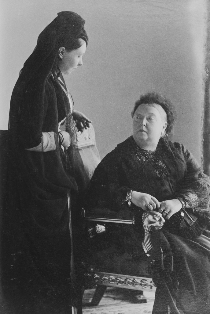 The Empress Frederick (left) stands, looking down at her mother, Queen Victoria, who is seated and looking up at her daughter. Both in mourning dress.