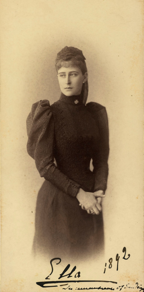 Photograph of Grand Duchess Elizabeth Feodorovna. She is standing with her head turned to the left and her hands clasped together. She is wearing dark mourning clothes with a cross at the collar. The photograph is annotated 'Ella 1892 In remembrance of Sandringham'. Grand Duchess Elizabeth Feodorovna, previously Princess Elisabeth of Hesse, married Grand Duke Sergei Alexandrovich in June 1884. In this photograph she is probably in mourning for her cousin Prince Albert Victor, Duke of Clarence and Avondale, who died at Sandringham in January 1892.
