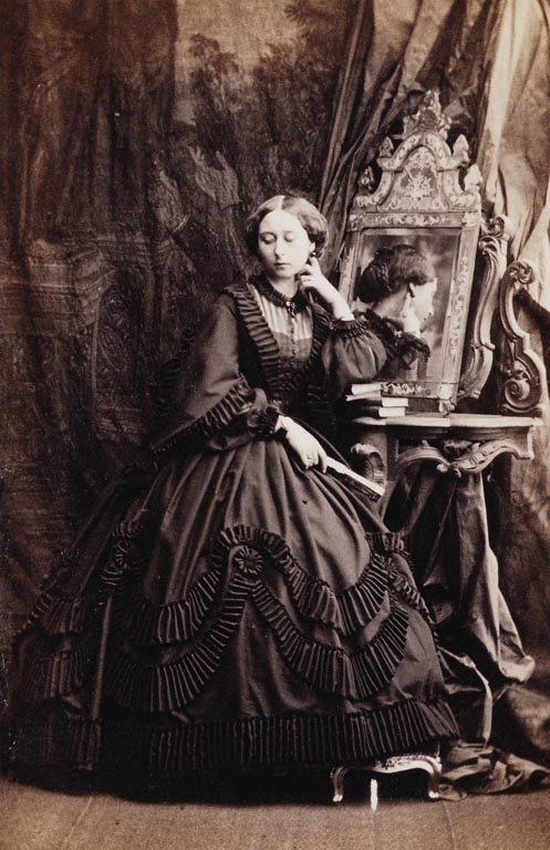 Photograph of Princess Alice, standing while resting her left elbow on some books piled on a console table with a mirror reflecting the left side of her head and her left hand. Princess Alice became engaged to Prince Louis of Hesse on 30 November 1860; their marriage took place in July 1862, having been postponed because of the death of the Prince Consort in December 1861. The Princess is wearing mourning in this photograph for her grandmother, the Duchess of Kent, who had died four months previously. Provenance Acquired by Queen Victoria