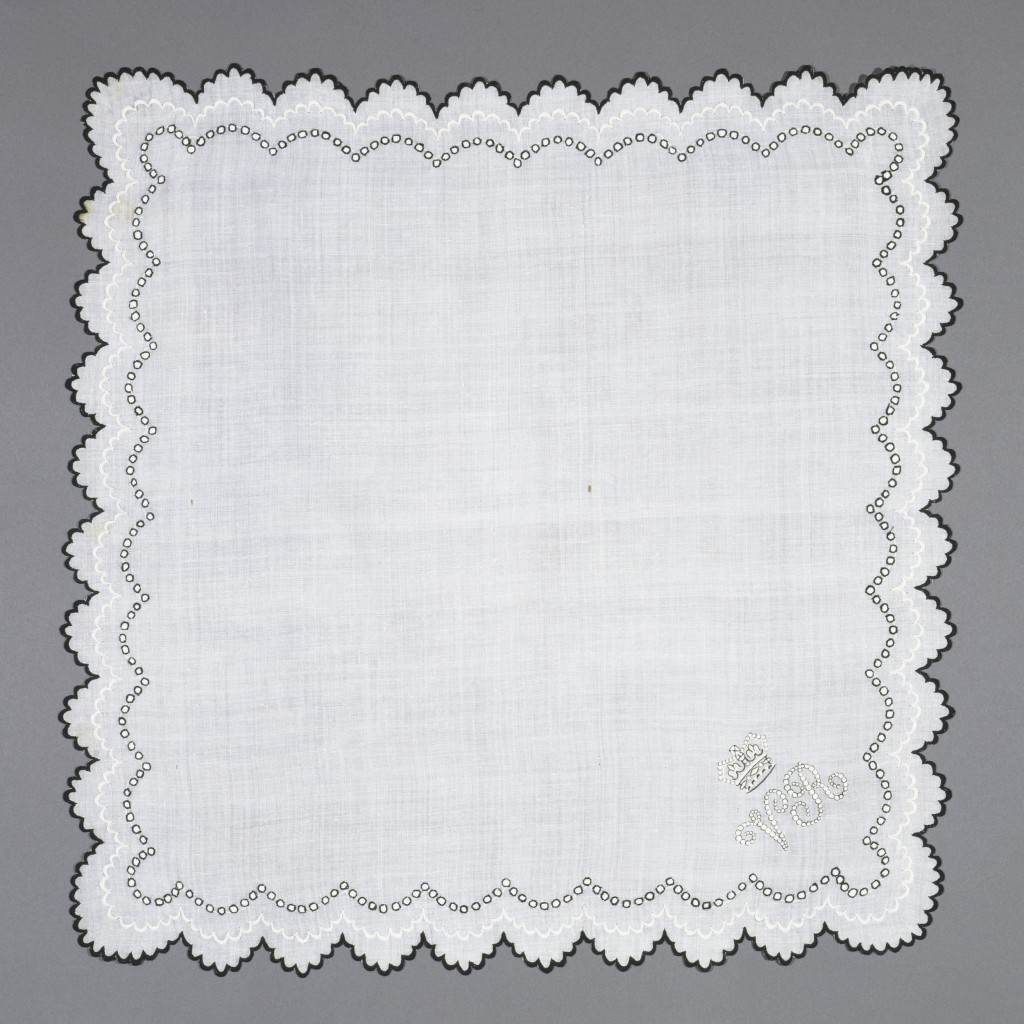 This mourning handkerchief was owned by Queen Victoria. It is made of the finest cambric linen and the embroidery shows her own cipher. Victorian etiquette ruled that widows went into deep mourning (called First Mourning) for a year and a day after the death of their husband. Some sources advised that during this time only black handkerchiefs should be used. This advice varied, and a complete list of clothes needed for respectable First Mourning, published in the 1881 issue of Sylvia's Home Journal included 'Twelve handkerchiefs with black borders, for ordinary use, cambric' and 'Twelve of finer cambric for better occasions'. Decoration, in the form of black edging, took a number of forms from plain printed or woven borders to black embroidery, as in this example, and narrowed as mourning diminished. It is not possible to date this handkerchief accurately. The depth of Queen Victoria's anguish on the death of Prince Albert meant that her mourning extended the usual periods acceptable and, as royalty, she set or flouted trends to suit herself. The handkerchief was given to the Museum along with other royal accessories by the Duke of Gloucester, a great grandson of Queen Victoria.